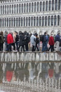 Group of people passing flooded St Mark's square in Venice.